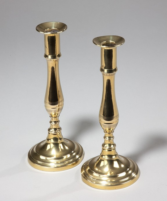 A fine pair of Regency period round base brass candlesticks. Large Image 1