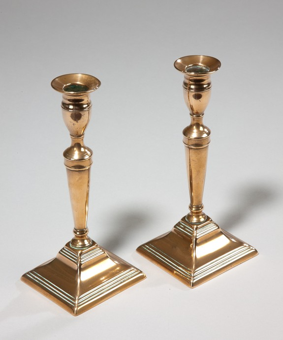 A fine pair of Georgian period square based brass candlesticks. Large Image 1