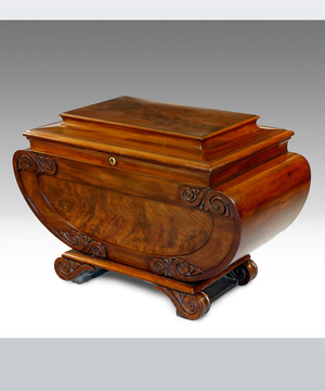 A fine Regency period sarcophagus shaped wine cooler veneered in highly figured mahogany.