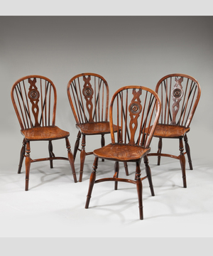 A set of four George III period yew and elm draught back Windsor chairs.