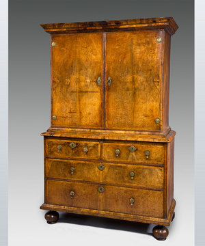 A well patinated Queen Anne period walnut veneered cabinet on chest.