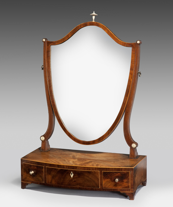 An elegant Sheraton period mahogany shield shaped dressing mirror.