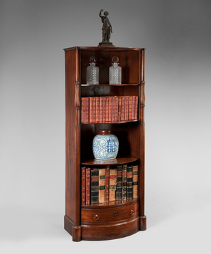 A rare Regency period mahogany open fronted bow shaped bookcase.