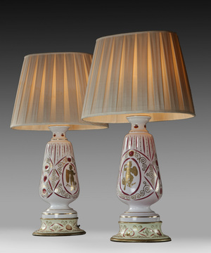 A pair of cream glazed lamps decorated with Grecian warriors.