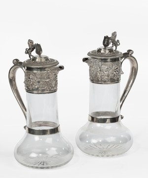 Pair of silver claret jugs with glass bodies.
