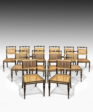 Set of twelve Regency dining chairs in ebonised and gilded decoration