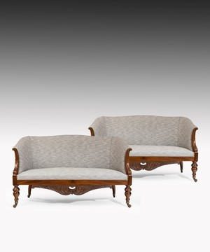 Pair of Charles X sofas with carved mahogany showwood frames.