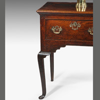 An antique George II oak dresser base with cabriole legs.