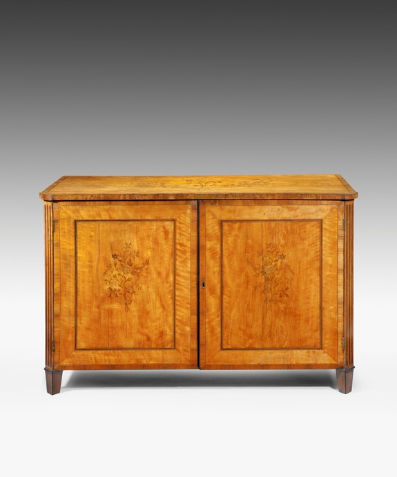 An antique Sheraton satinwood cabinet.