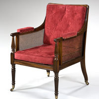 An antique Sheraton mahogany bergere armchair.