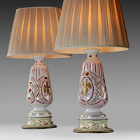 A pair of cream glazed lamps decorated with Grecian warriors. Thumbnail 1