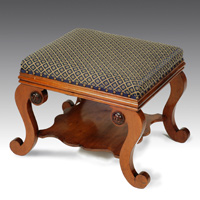 An antique Regency mahogany stool with scrolling legs.