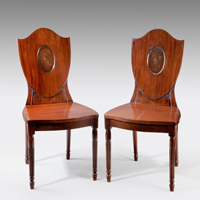 A pair of antique Hepplewhite hall chairs.