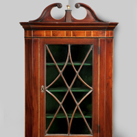 An antique Sheraton corner cupboard.